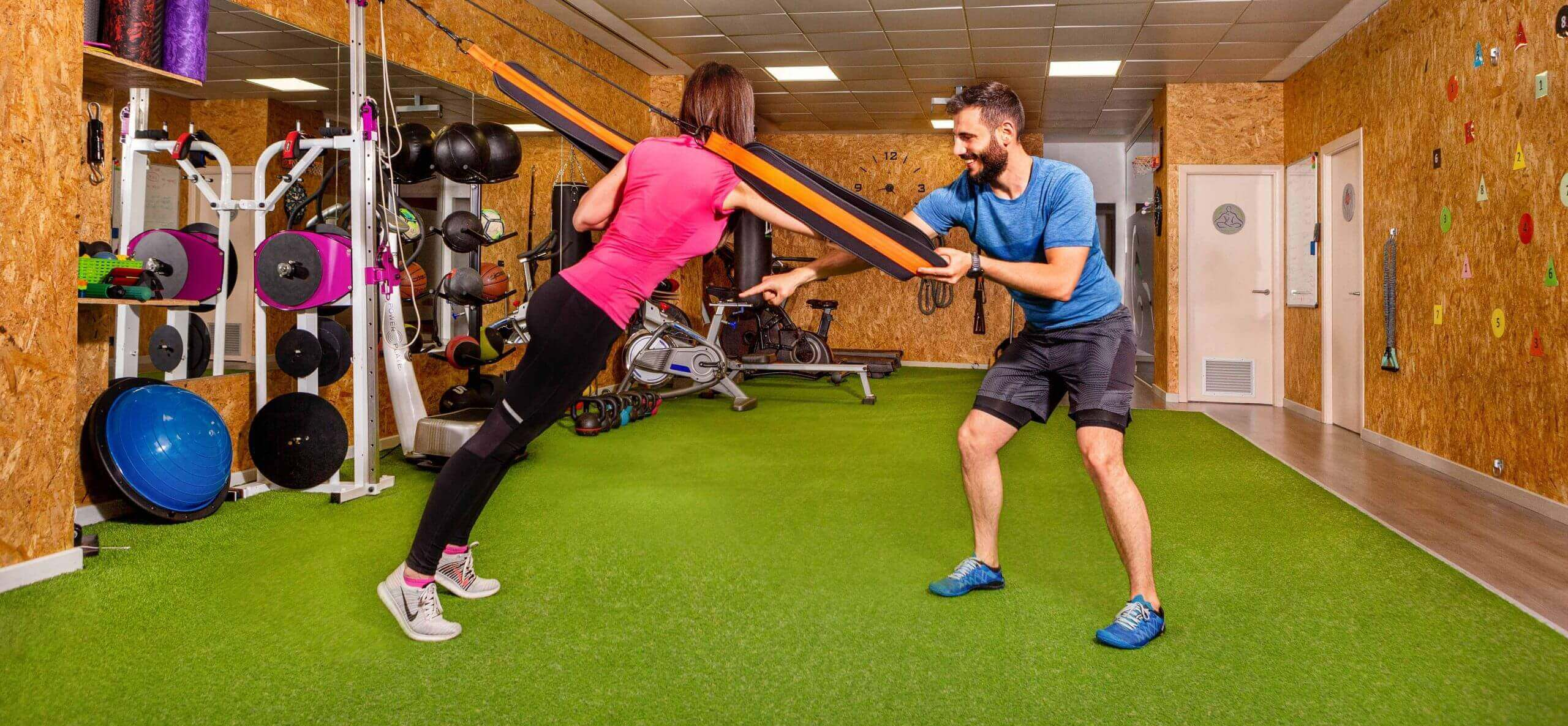 imagen de un entrenador corrigiendo un ejercicio a una chica