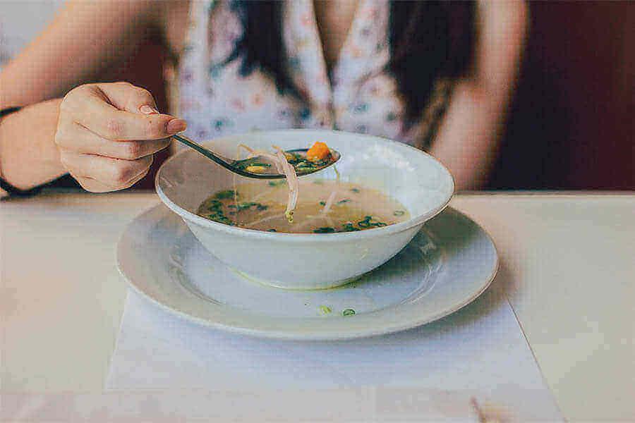 mujer comiendo una sopa de verduras